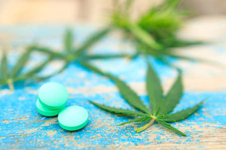 three round green pills near cannabis leaves on wood background