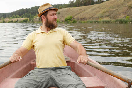 bearded adult man rowing oars while sitting in a boat. rowboat ride develops arms
