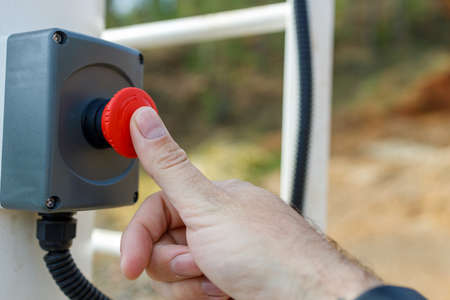 a thumb on a man's hand presses a red button on a signal panandy outdoors. emergency call 免版税图像