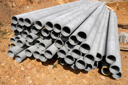 a dump of concrete gray pipes in large quantities on clay soil. during construction 免版税图像