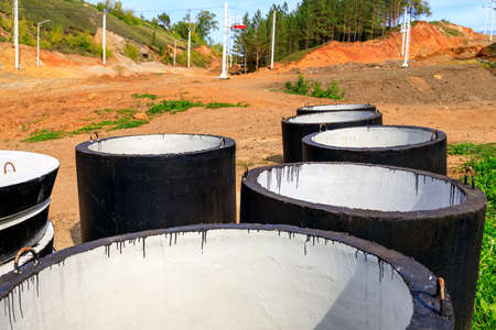 large black concrete pipes painted with bituminous paint. elements for the construction of a water supply system 免版税图像
