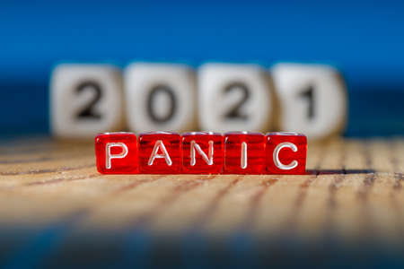 Panic is assembled from letters on red plastic cubes at the back out of focus 2021. concept 2021 time to panic everything will be bad 免版税图像
