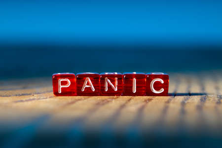 the word panic made of letters on red cubes on a wooden surface. background blue
