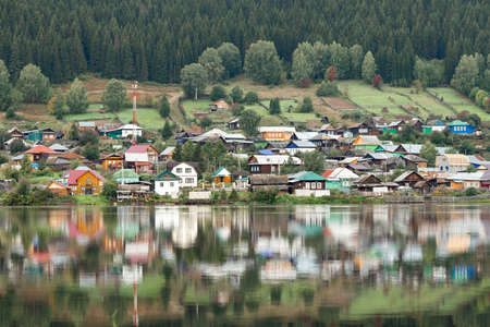 Verkhniye Sergi, Russia - September. 06 2020 steep opposite bank with wooden simple houses in a Russian village 新闻类图片