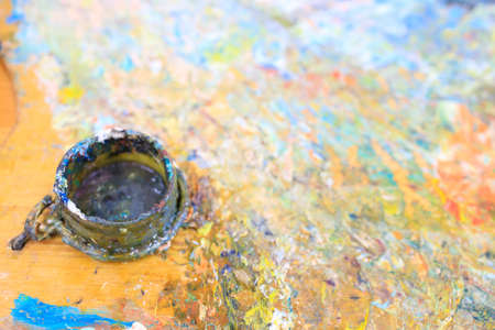 out of focus paint jar and paint mixing board after artist's work 免版税图像