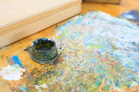 a jar of paint left at the workplace of an artist painting a picture with paints 免版税图像