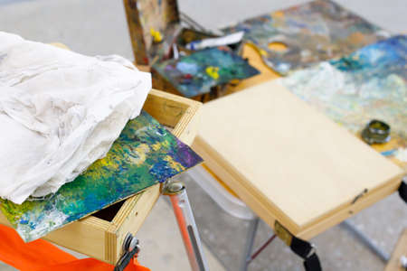the artist's tools are collected in wooden crates, a palette of rags and easel stands 免版税图像
