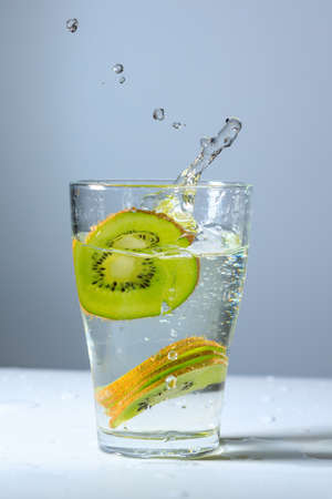 stopping the movement of sliced kiwi slices falling into a glass of water. fruit in water