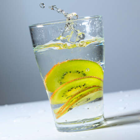 sliced kiwi fruit in a glass of water, glass tilted 免版税图像