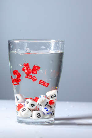 cubes with letters and numbers are submerged in water, letters and numbers are drowned in a glass of water 免版税图像