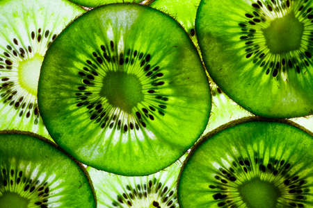 sliced kiwi fruit in round slices laid out on the table with transparent lighting on the other side