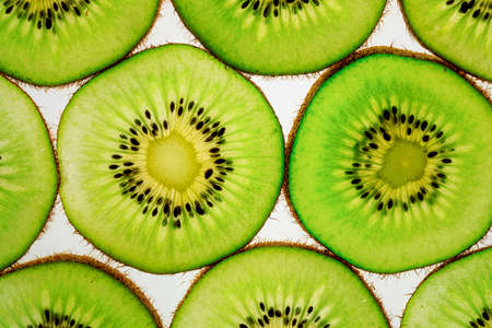 sliced pieces of kiwi fruit laid out on a white background, many pieces of a round shape 免版税图像