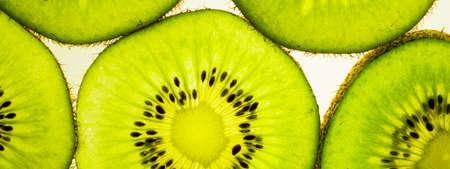 banner of sliced kiwi slices on a white table, backlit green color 免版税图像
