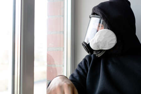 a man in a gas mask and a black hood looks out the window sitting against the wall. protection against chemical attack and radiation