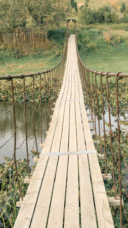 vertical photo of a suspension bridge over a small river in the summer. metal railings and wooden bridge
