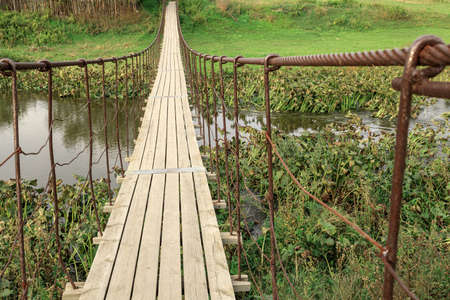 a wooden suspension bridge over a river with plants, an overgrown river and a bridge in the summer