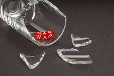 on the verge of a broken glass, the word war, red cubes on which the word war is assembled in letters