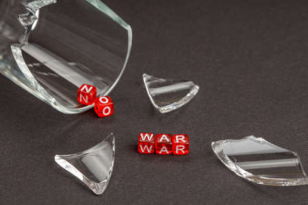 broken glass of glass scattered around, next to red cubes on which the letters are not war. cancellation of hostilities concept