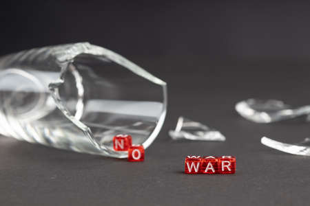 from the broken glass the words no war are poured out next to broken glass and fragments. dark background out of focus