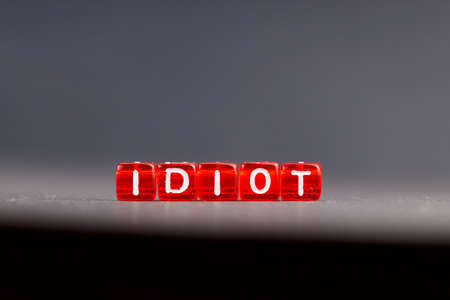 the word idiot is assembled from letters on red squares. background dark