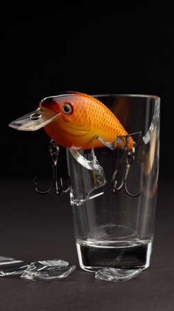 vertical photo fishing orange bait with hooks on the edge of a glass beaker. dark background 免版税图像
