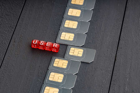top view of a row of sim cards and red cubes with the inscription user. selection of a user from a set
