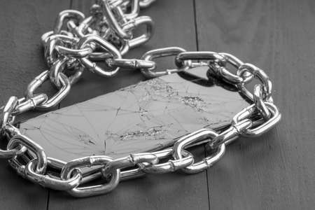 broken phone surrounded by steel chain, property protection 免版税图像