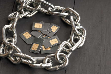 steel chain surrounds sim cards collected in a bunch in one place, protecting the data of users of cellular operators