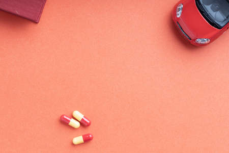 part of auto toy pill medical and corner of book on red background 免版税图像