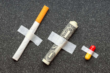 a cigarette with a dollar and a pill fixed with tape to a stone surface. smoke then buy medicine Banco de Imagens