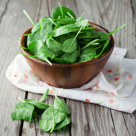 Baby spinach leaves in a bowl on dark wooden background, selective focus