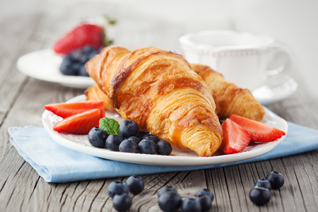 french bread rolls: Delicious breakfast with fresh croissants and ripe berries on old wooden background