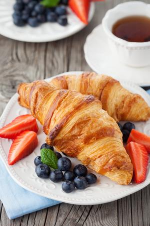 焼きたてのクロワッサン、古い木製の背景に熟した果実とおいしい朝食