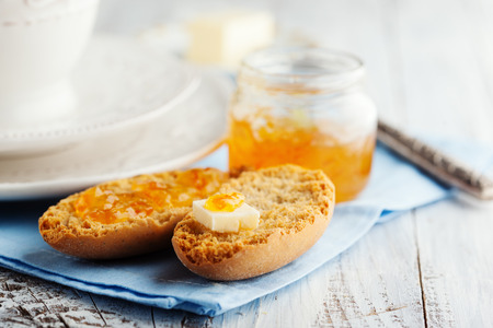 Morning breakfast with crackers and orange marmalade on white wooden table photo