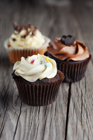 cupcakes: Fresh chocolate cupcakes decorated with creamy vanilla cream on old wooden background, selective focus