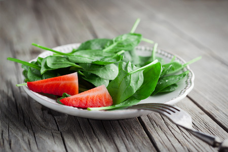 Baby spinach leaves with fresh strawberries on dark wooden background, selective focus