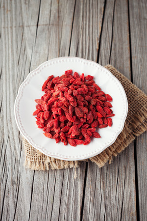 tibet bowls: Plate with dried himalayan goji berries on old wooden background