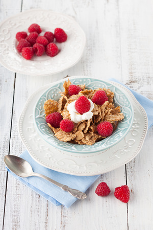 Healthy breakfast with wholegrain flakes, milk and fresh berries on white wooden table, selective focus photo
