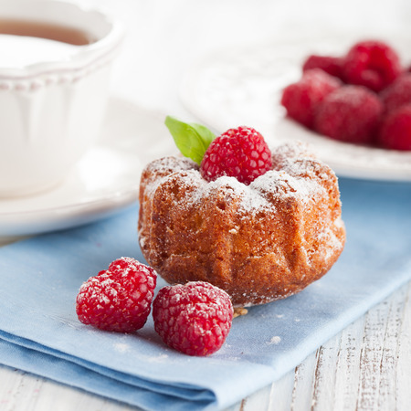 Homemade muffin with a fresh raspberries and cup of tea on white wooden background, selective focus photo