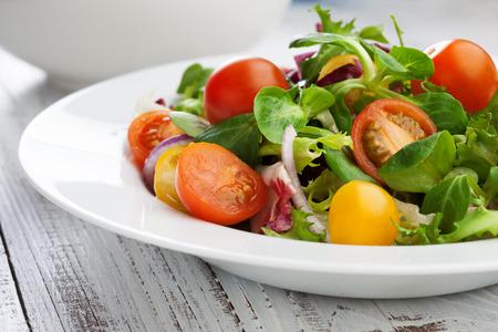 チェリー トマトとバジルのサラダ葉板の白い木製テーブル 写真素材