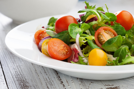 Fresh salad with cherry tomatoes and basil leaves in a plate on white wooden table