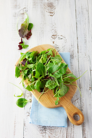 Fresh green salad with spinach, arugula, romaine and lettuce on a wooden chopping board on rustic white background, top view