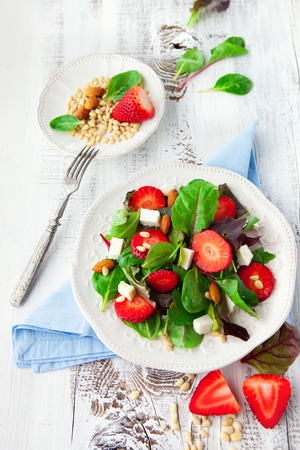 Fresh salad with strawberries, spinach leaves and feta cheese on white wooden background, selective focus 스톡 콘텐츠