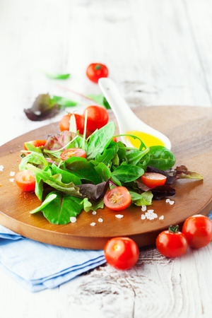 Fresh salad with cherry tomatoes, spinach, arugula, romaine and lettuce on a wooden chopping board on rustic white background, selective focus Stockfoto