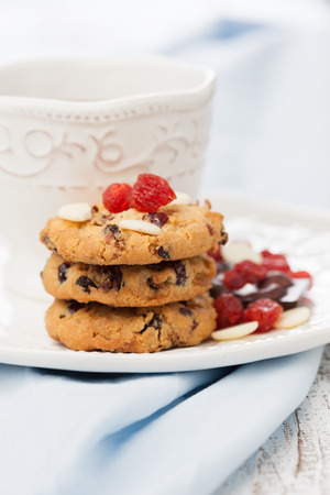 glass cutter: Fresh homemade cookies with cranberries and cup of tea on a table