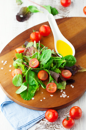 Fresh salad with cherry tomatoes, spinach, arugula, romaine and lettuce on a wooden chopping board on rustic white background, selective focus photo