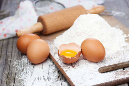 Baking ingredients - flour, eggs and rolling pin on a table