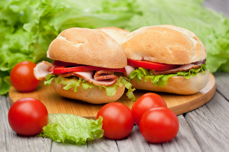 Fresh and tasty sandwiches with ham, tomatoes and fresh green lettuce on wooden table