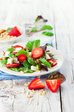 Fresh salad with strawberries, spinach leaves and feta cheese on white wooden background, selective focus Stockfoto