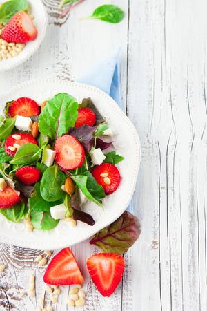 Ensalada fresca con fresas, hojas de espinaca y queso feta sobre fondo blanco de madera, enfoque selectivo Foto de archivo - 38444391